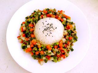 肉末三丁盖浇饭,把肉末三丁盛到盘子里,在米饭上面撒少许熟黑芝麻