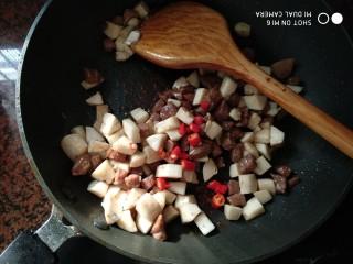 杏鲍菇牛肉粒,再加入杏鲍菇粒、红辣椒粒,翻炒至杏鲍菇变软