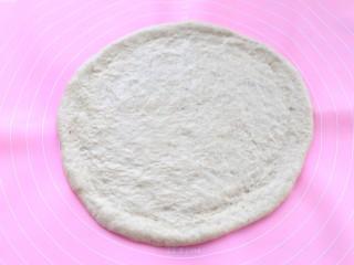 香蕉芒果披萨——九寸,将面团取出揉匀排气后,覆盖保鲜膜松弛20分钟,然后用擀面杖擀成中间薄边缘厚的饼皮
