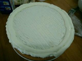 酸奶淋面蛋糕,取一半的奶油倒在蛋糕上,用刮板刮出纹路。剩下的一半装到裱花袋,剪个口,在蛋糕周围挤一圈奶油。