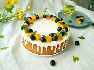 酸奶淋面蛋糕,在蛋糕周围摆上一圈水果,再放上薄荷叶装饰。