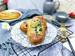 香葱培根芝士面包,戴上隔热手套将烤盘取出,立即刷上一层玉米油,这样会更好的锁住面包的水份。