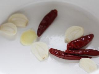 深夜食堂之酒蒸花蛤,油微微加热后放入姜片、蒜片和红干椒,翻炒爆香防止焦糊