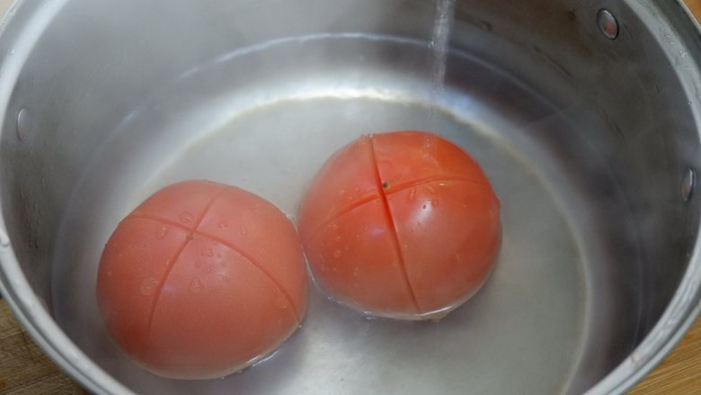 番茄炒西葫芦,锅中烧开水,将西红柿放进去焯烫一下