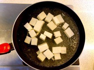 蟹黄豆腐,锅中下水煮开,放少量盐,加入豆腐焯水5分钟。这样既可以去豆腥味又能保持豆腐形状不易破碎。 焯水后取出沥干水分。