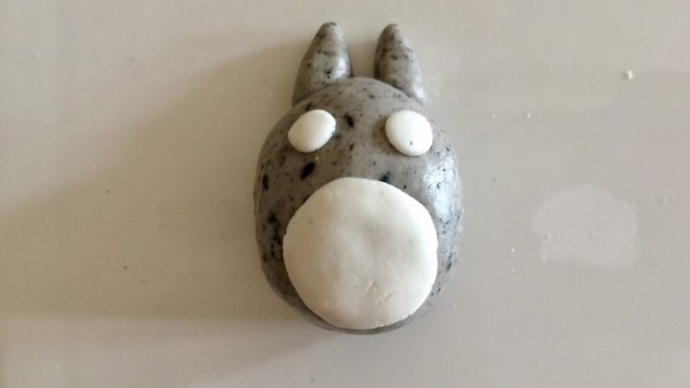 萌萌哒龙猫汤圆,取两个1.5克左右的灰色粉团,捏出两个耳朵。用白色粉团捏出肚皮和眼睛。
