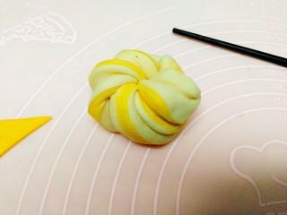 双色南瓜花卷,用手拉起两端,拉长扭成麻花状,在手中打个结,做成花团状备用。