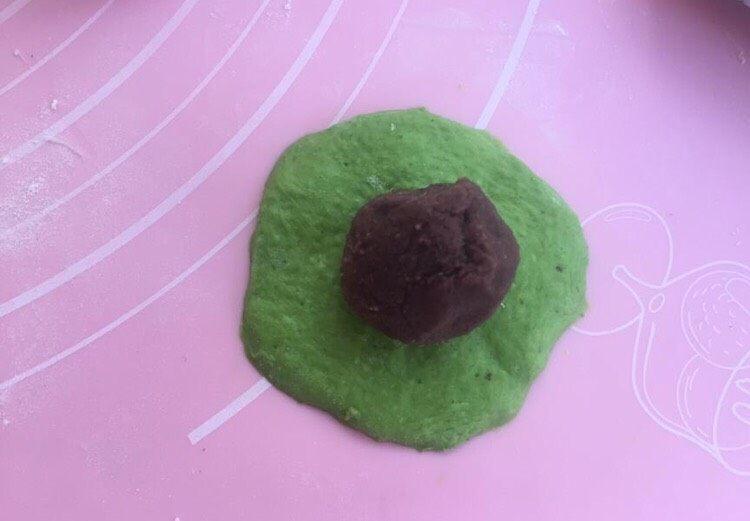 三色夹心小餐包,先擀圆绿色面团,包入豆沙馅