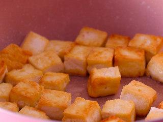 酸菜豆腐,豆腐块煎至两面金黄后装盘备用