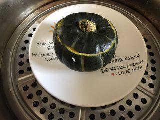 一人食 南瓜杂粮饭,盖上南瓜盖,将南瓜放在一个盘子上,蒸锅加满水