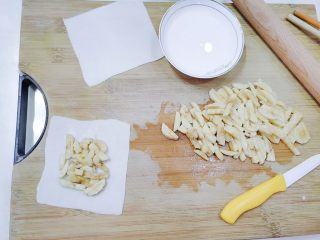 嫩脆香蕉派,冷藏好的饺子皮拿出来,铺一张在下面,把香蕉碎放上去,四周留边。
