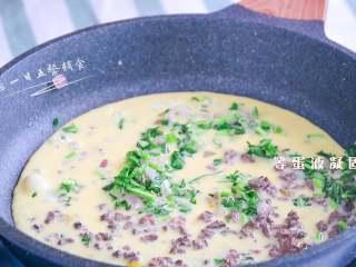 猪肝茼蒿炒鸡蛋,蛋奶液加入,等底部蛋液凝固。