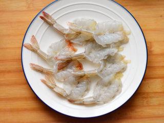 鲜虾天妇罗,去好虾线后,从中间部位切开,摆放在盘子里,加入胡椒粉和3克盐腌制10分钟。