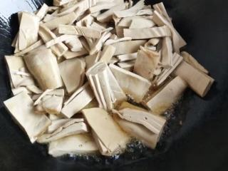 砂锅菠菜烧豆腐皮,锅里入油,加入豆腐皮用油煎