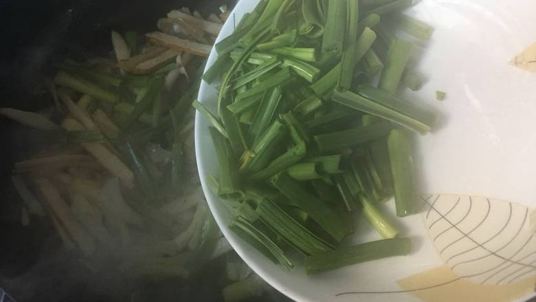 咸肉香干炒青蒜,倒入蒜叶,翻炒;