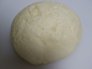 椰蓉花朵面包,将面团取出按压排气,边缘的大气泡拍掉。