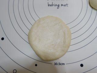 椰蓉花朵面包,收口向下,用擀面杖擀大擀薄一点。擀好放在烤盘上。