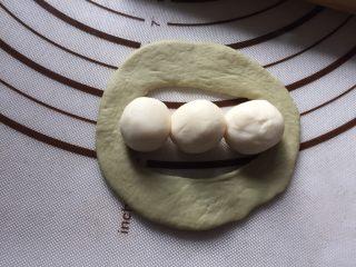 豌豆荚造型馒头,再将面皮展开,在中心缺口上,放三颗白色小球
