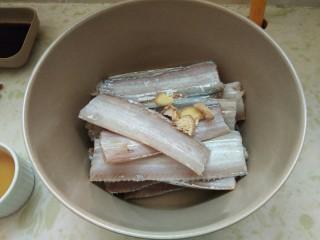 酒香煎带鱼,找一个干净无水无油的大碗,把一盘带鱼放里面然后下入姜片。