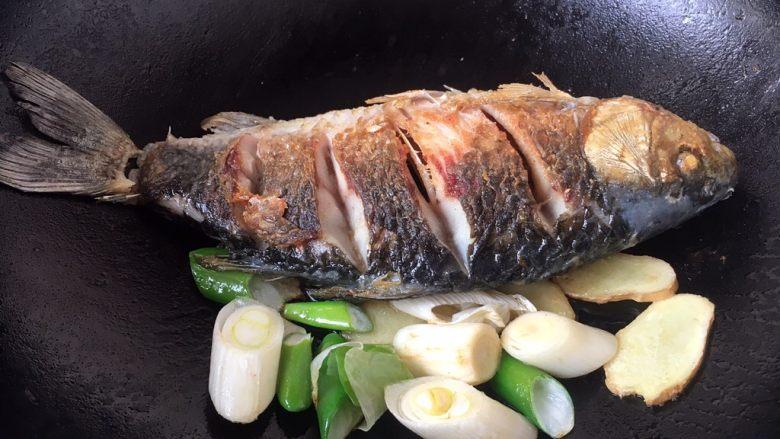 鲫鱼豆腐汤,将煎好的鱼扒在锅的一边,放入葱段和姜片,煸出香味。