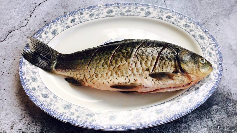 鲫鱼豆腐汤,把鱼的两面都切斜刀,在鱼的两面抹少许盐,腌制10分钟。