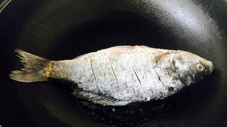 鲫鱼豆腐汤,大火起锅,锅热放入少许的油,当油六成热时放入鱼,此时改中火。 煎鱼时随时微微调整火的大小,千万不要让油起烟。往油锅里放鱼时,用双手分别拎住鱼头和鱼尾,贴着油面轻轻地放入。 我使用的是不粘锅。 如果小伙伴们使用的是铁锅就要把锅烧的热热的,然后用姜在锅里涂抹一层,再继续操作。