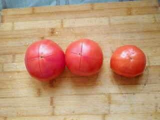 西红柿炖牛肉,在西红柿上面用刀划一个十字。方便西红柿去皮。