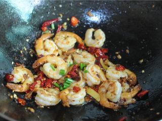 宫保凤尾虾,待虾仁慢慢变色成球状后将炒好的干辣椒段、生姜片、蒜末倒进去,淋入备好的调味汁炒至变稠,倒入熟花生米稍微翻拌即可