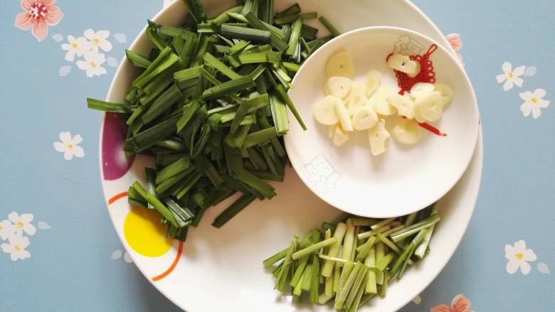 春天的味道-韭菜炒银芽,韭菜切小段,菜叶与菜茎分开放置,蒜切片,韭菜叶和茎的成熟度不同,所以要分开放置,分先后顺序下锅。