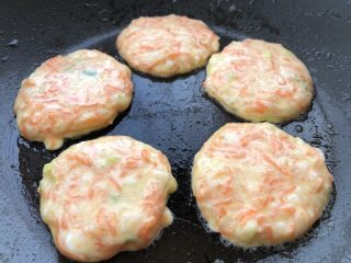 胡萝卜鸡蛋虾肉饼,热锅刷油,开小火,用小勺舀一勺糊糊放入锅里,并迅速摊平。