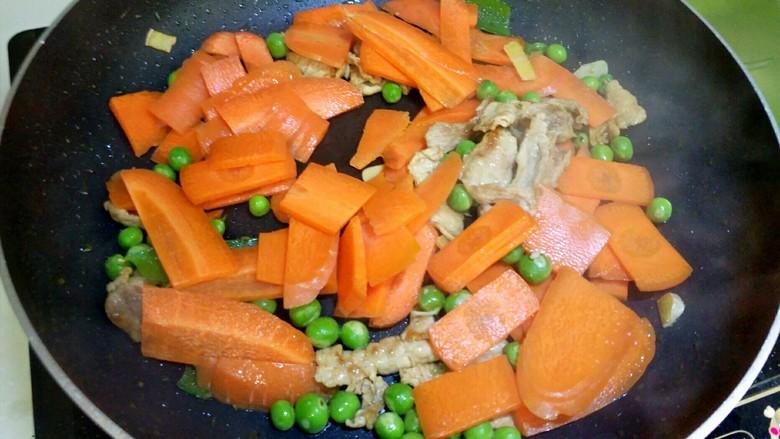 胡萝卜炒豌豆,待水煮干,加入胡萝卜,翻炒1分钟。