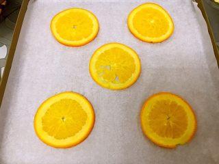 橙香蛋糕卷,烤盘垫油纸摆上橙子片
