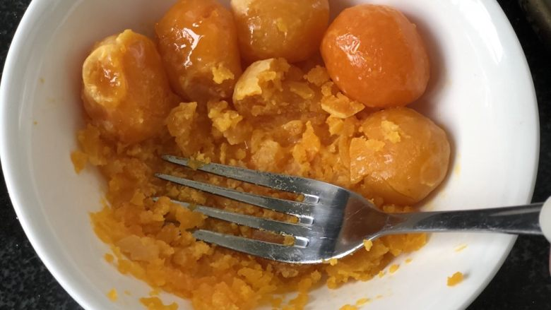 时令菜谱-网红艾草青团,新鲜咸鸭蛋磕出蛋黄,上锅蒸熟,用叉子压碎。