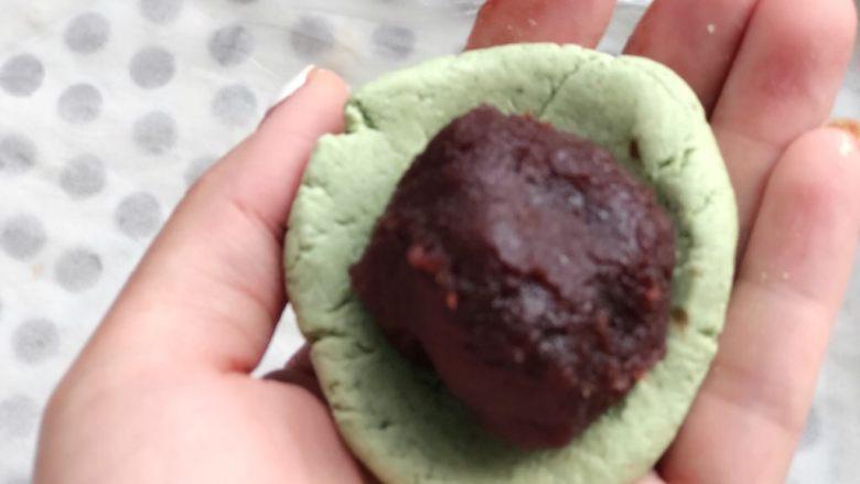时令菜谱-网红艾草青团,再压扁,用大拇指在中间按出一个窝,放入馅料。