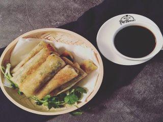 薄油煎春卷,盘内垫上吸油纸,吸去多余的油脂,再搭配一杯黑咖啡,香脆解腻。