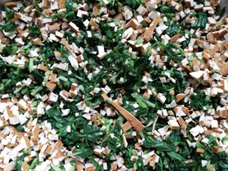 香干拌马兰,香干也切碎,放入盛有马兰的容器里稍微搅拌。