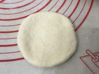 豆沙花朵小餐包, 取一个松弛好的面团用擀面杖从中间向四周擀开,边上的气泡用手拍打掉