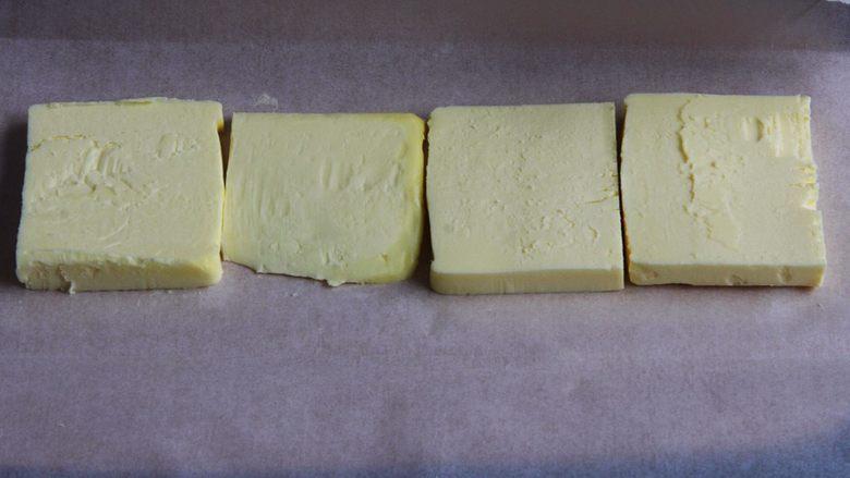 起酥面包,面团发酵中,拿出融软的黄油,切成片。