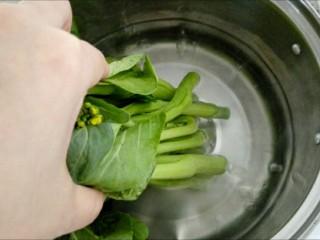 香菇菜心,锅中水烧开,加入少许盐,食用油。妙招一:用手抓住菜心尾部,先将根部浸入水中,焯烫,再逐渐把叶子部分浸入水中焯烫。然后迅速捞出过凉水。根部焯烫时间和尾部叶子部分不同,这样可以避免菜叶焯烫时间过长,而根本还没焯烫熟。