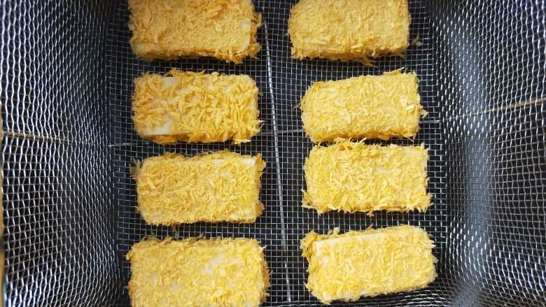 酸酸甜甜炸鹰嘴豆糕,裹好面包糠的鹰嘴豆糕放滤网里。