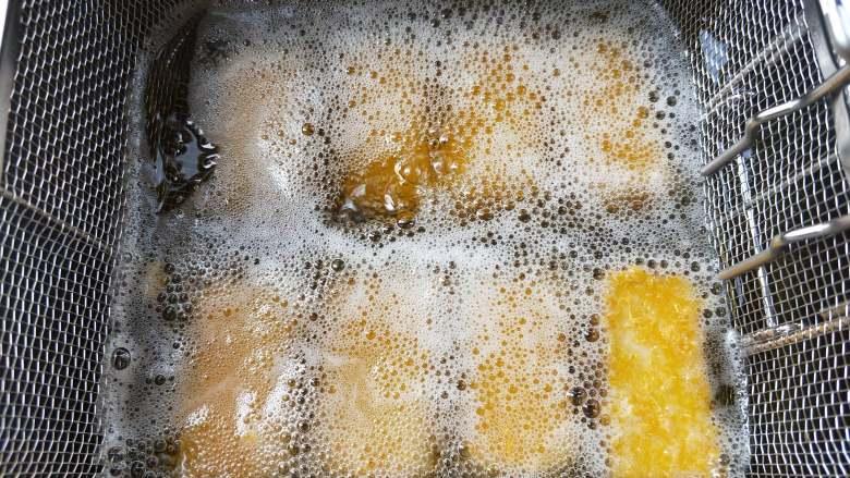 酸酸甜甜炸鹰嘴豆糕,滤网放入油锅,将鹰嘴豆糕炸至金黄色。