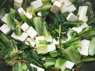 莴苣叶炒豆腐,轻轻摇晃炒锅,以免把豆腐翻碎,加适量盐调味,关火。