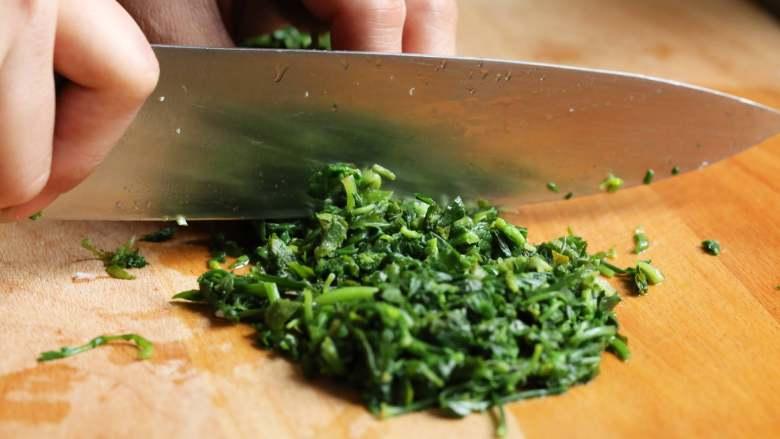 荠菜春笋炒年糕,荠菜用凉水冲凉,挤干水分,切成细末待用。