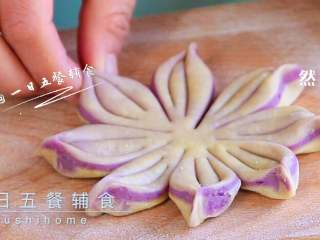 紫薯花朵馒头,再用刀背在每一份中间压2道印痕,别太用力切断了。然后把相邻切口捏起来,就是一个个花瓣。