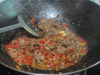 剁椒牛肉,此时改用大火,将事先炒好的牛肉加入,倒入料酒进行翻炒,让剁椒、蒜、葱炒的香味充分渗入牛肉中