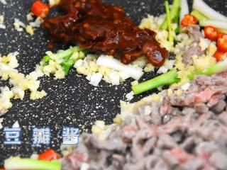 芹菜牛肉,变色的牛肉丝推至锅中的另一边,空出来的地方倒入葱白、小米椒、姜蒜末,一起炒香后再加入豆瓣酱和肉丝炒至上色。