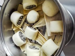 黑芝麻馒头卷,面团下面垫玉米皮,放入蒸锅中,蒸锅提前放入足量的清水,盖锅盖醒发15-20分钟