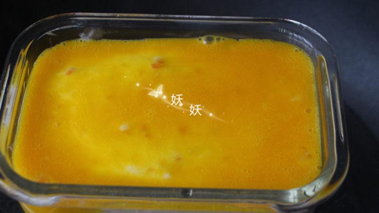 南极磷虾蒸虾糕,倒入蛋黄液。继续盖上保险膜,再蒸5分钟。
