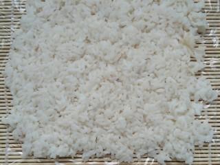 不拘一格吃寿司,将米饭平铺在保鲜膜上,记住按压整齐哦。