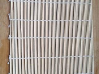 不拘一格吃寿司,将卷寿司的帘子平铺在案板上。